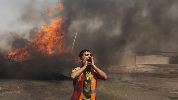 Palestinian calls for fire-fighters to extinguish a fire which police said was caused by an Israeli tank's shelling in the industrial area in the east of Gaza City