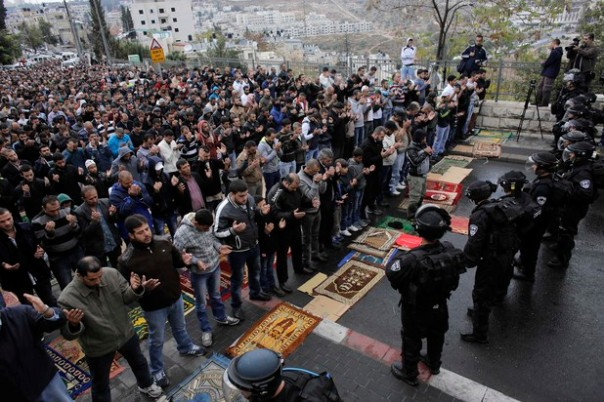 Israeli security forces stand guard as Palestinian Muslim worshippers perform traditional Friday prayers on a street